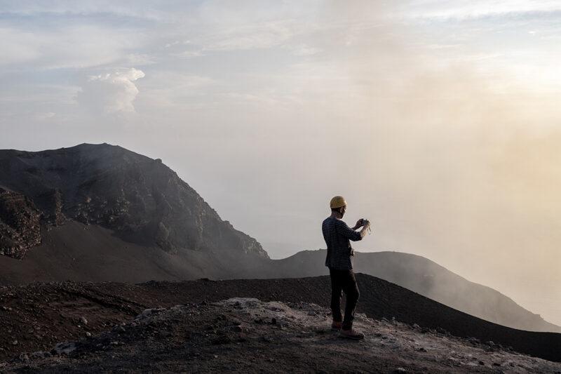 paesaggio vulcanico con persona di spalle che lo fotografa
